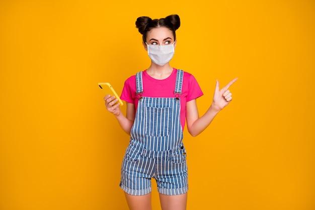 Portret van haar, mooi, aantrekkelijk, gezond, zelfverzekerd meisje dat een cel gebruikt met een veiligheidsmasker dat mers cov influenza aantoont, kopieerruimte geïsoleerd helder levendig glans levendige gele kleur achtergrond