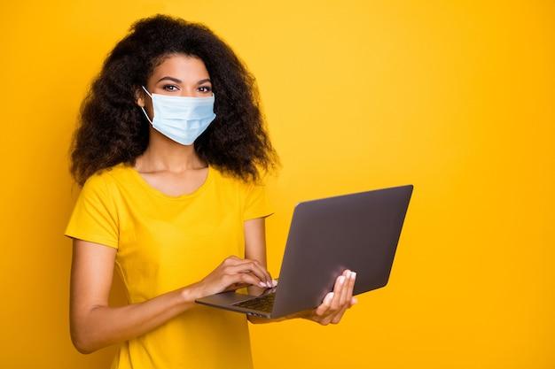 Portret van haar, mooi, aantrekkelijk meisje met golvend haar dat laptop gebruikt die gaas veiligheidsmasker draagt bestelling thuisbezorging goederen ziektepreventie geïsoleerd helder levendig glans levendige gele kleur achtergrond