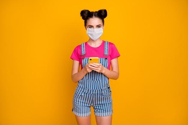Portret van haar mooi aantrekkelijk mooi meisje met behulp van apparaat wi-fi dragen veiligheidsmasker thuis blijven mers cov griep preventie geïsoleerd helder levendig glans levendige gele kleur achtergrond