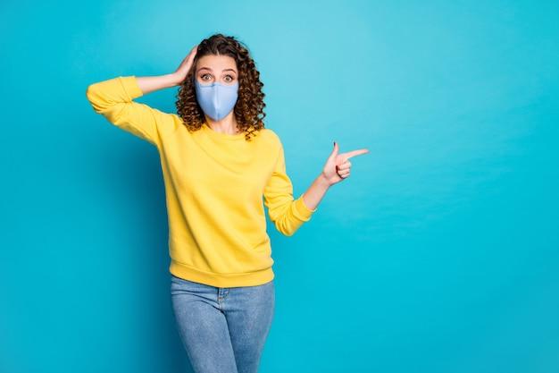 Portret van haar, mooi, aantrekkelijk, verbijsterd, golvend meisje met een herbruikbaar veiligheidstextielmasker dat nieuwigheid aantoont kopieerruimte geïsoleerd helder levendig glans levendige blauwe kleur achtergrond