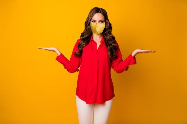 Portret van haar, mooi uitziend, aantrekkelijk meisje met golvend haar dat een herbruikbaar textielmasker draagt dat handpalmen vasthoudt kopieer ruimte mers cov geïsoleerd helder levendig glans levendige gele kleur achtergrond