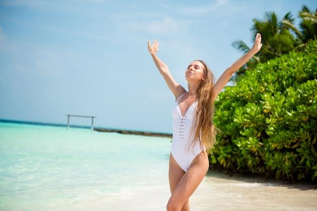 Portret van haar, mooi uitziende, dromerige, vredige, sportieve, slanke meid die gaat genieten van een zonnige warme dag azuurblauwe zee schone pure plage bali zomerweekend opstaan handen in de frisse lucht