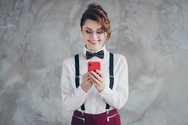 Portret van haar, mooi uitziende, mooie, mooie, stijlvolle, gefocuste, vrolijke, blije meid met golvend haar die digitaal apparaat gebruikt dat over grijze betonnen industriële muurachtergrond wordt geïsoleerd