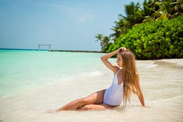 Portret van haar mooi uitziende, perfecte, slanke langharige meid zittend op plage genietend van zonnige warme dag schoon helder transparant water aan zee open frisse lucht