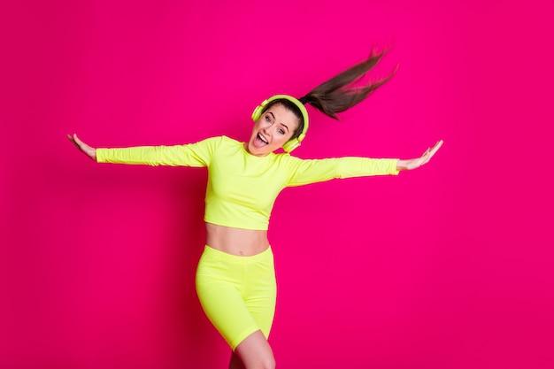 Portret van haar, mooi, zorgeloos, vrolijk, vrolijk meisje dat pop rockmuziek luistert en geniet van dansen met plezier voor de gek houden geïsoleerde heldere levendige glans levendige roze fuchsia kleur achtergrond