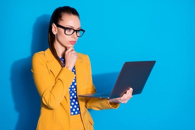 Portret van haar mooie aantrekkelijke charmante chique stijlvolle gefocuste dame partner leider ceo baas chef bedrijf in handen laptop browsen rapport geïsoleerd helder levendig glans levendige blauwe kleur achtergrond