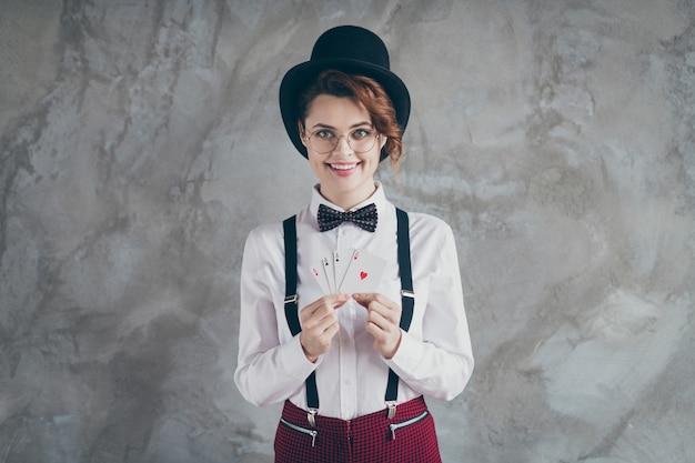 Portret van haar mooie aantrekkelijke mooie mooie stijlvolle vrolijke vrolijke golvende haren meisje omgaan met papieren kaarten blackjack geïsoleerd op grijze betonnen industriële muur achtergrond