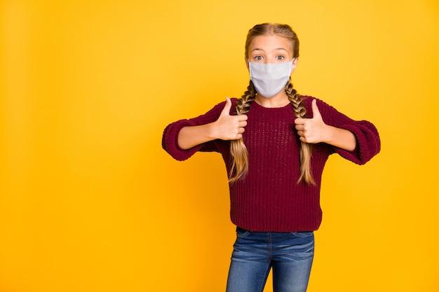 Portret van haar mooie aantrekkelijke pre-tiener meisje met veiligheidsmasker met dubbele thumbup herstel therapie kopie ruimte advertentie vaccin geïsoleerd heldere levendige glans levendige gele kleur achtergrond