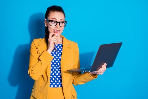 Portret van haar, mooie, aantrekkelijke, twijfelachtige dame die in handen laptop vasthoudt en besluit tot het maken van een ideeplanontwikkeling geïsoleerd op een heldere, levendige glans, een levendige blauwe kleurachtergrond