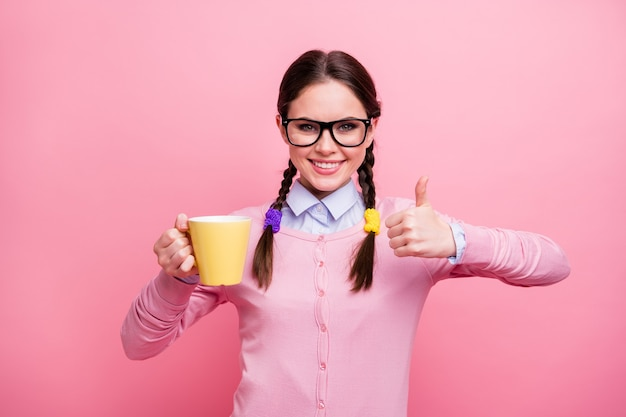 Portret van haar mooie aantrekkelijke vrij vrolijke vrolijke inhoud intellectuele bruinharige tienermeisje drinken cacao weergegeven: thumbup advertentie advies geïsoleerd op roze pastel kleur achtergrond