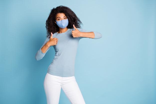 Portret van haar mooie, mooie, gezonde vriendin die duim omhoog laat zien met een herbruikbaar veiligheidsmasker, stop pandemie, china wuhan, ziektebehandeling, geïsoleerde pastelblauwe kleurachtergrond