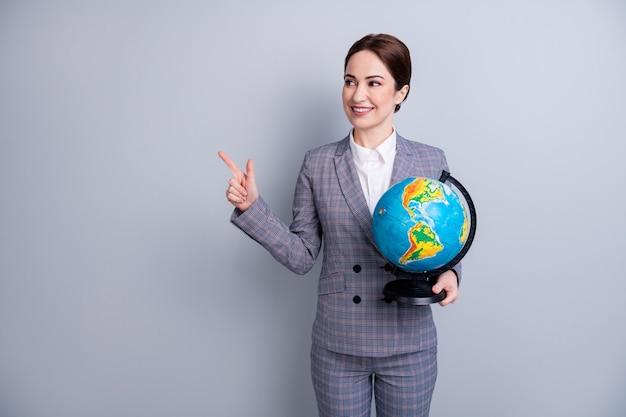 Portret van haar mooie, slimme, slimme, bekwame, vrolijke, specialistische leraar die in handen globe houdt en de kennis van de advertentieruimte van de kopie demonstreert geïsoleerd op een grijze pastelkleurige achtergrond
