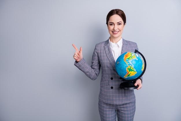 Portret van haar mooie, slimme, slimme tutor draagt een geruit pak in handen globe demonstreren kopie lege lege ruimte advertentie-informatie geïsoleerd op grijze pastel kleur achtergrond