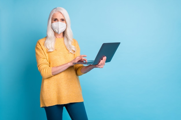 Portret van haar mooie succesvolle oudere grijsharige vrouw met behulp van laptop met n95 veilig masker stop mers cov grippe infectie blijf thuis geïsoleerd helder levendig glans levendige blauwe kleur achtergrond