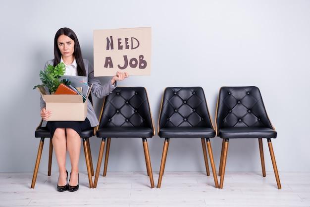 Portret van haar ze aantrekkelijk depressief ontslagen werkloze dame office manager zoeker zittend in een stoel houden in handen poster nodig een baan woorden bedrijf kostenreductie geïsoleerde pastel grijze kleur achtergrond