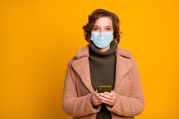 Portret van haar ze aantrekkelijk meisje met veiligheidsmasker met behulp van apparaat lees blader nieuws mers cov ziekte besmettelijke virale longontsteking griep geïsoleerde heldere levendige levendige gele kleur achtergrond
