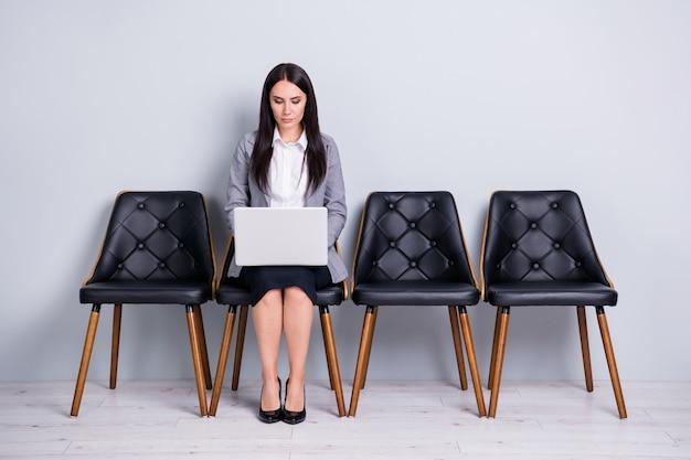 Portret van haar ze aantrekkelijke stijlvolle gerichte dame agent makelaar leraar docent professor zittend in de stoel met behulp van laptop voorbereiding markt presentatie rapport plan geïsoleerde pastel grijze kleur achtergrond