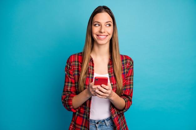 Portret van haar, ze is aardig, aantrekkelijk, charmant, vrolijk, vrolijk langharig meisje met een geruit overhemd met behulp van digitale cel geïsoleerd over heldere levendige glans levendige blauwe kleur achtergrond