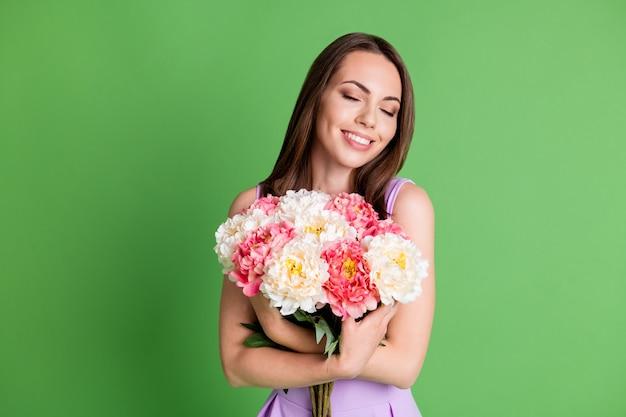 Portret van haar, ze is aardig, aantrekkelijk, mooi, charmant, dromerig, vrolijk meisje dat geniet van vakantiegelegenheid en in handen ruikt aan verse bloemen, geïsoleerde groene kleur achtergrond