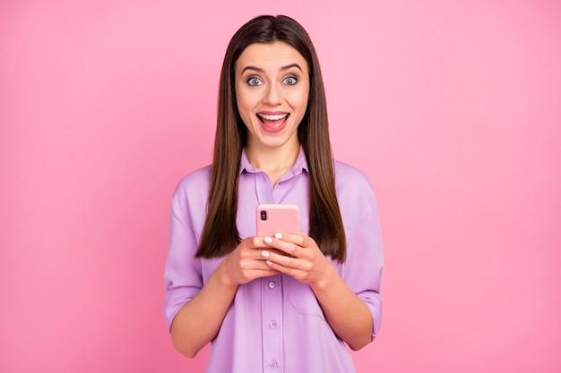 Portret van haar, ze is aardig, aantrekkelijk, mooi, charmant, verbaasd, blij, verslaafd, vrolijk, langharig meisje dat een cel gebruikt die plezier heeft geïsoleerd over roze pastelkleurige achtergrond