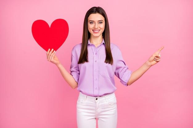 Portret van haar, ze is aardig, aantrekkelijk, mooi, charmant, vrolijk, langharig meisje met in de hand een groot groot papieren hart met advertentiekopieerruimte geïsoleerd op roze pastelkleurige achtergrond