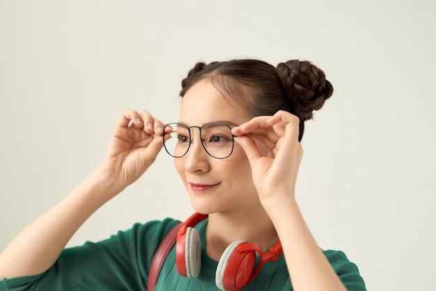 Portret van haar, ze is aardig, schattig, lief, mooi, aantrekkelijk, vrolijk, vrolijk, ontroerende bril die over wit wordt geïsoleerd
