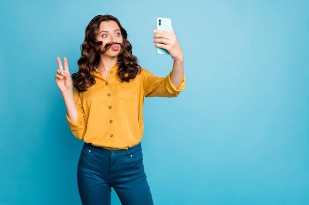 Portret van haar, ze is een leuke aantrekkelijke komische funky vrolijke dame met golvend haar die een selfie neemt en een v-teken grimassen toont.