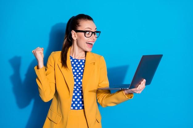 Portret van haar ze leuk aantrekkelijk mooi chique tevreden vrolijke vrolijke blije dame in handen houden laptop vreugde winnende inschrijving geïsoleerde heldere levendige glans levendige blauwe kleur achtergrond