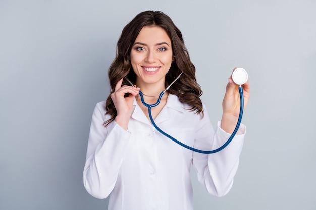 Portret van haar ze mooi aantrekkelijk mooi vrolijk vrolijk golvend meisje doc luisteren adem medische verzekering bijstand infectie geïsoleerd over grijze pastelkleur achtergrond