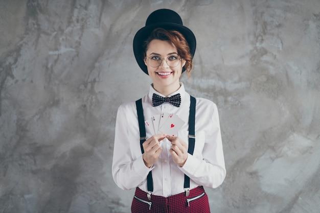 Portret van haar ze mooi aantrekkelijk mooi vrolijk vrolijk golvend meisje in handen te houden papieren kaarten aas blackjack vrije tijd jackpot geïsoleerd op grijze betonnen industriële muur achtergrond