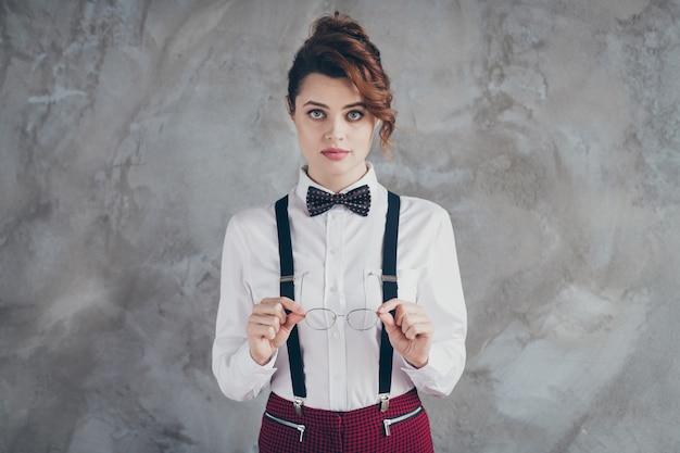 Portret van haar ze mooi uitziende aantrekkelijke inhoud stijlvolle slimme slimme serieuze golvend-haired meisje dame in handen houden specs geïsoleerd op grijze betonnen industriële muur achtergrond