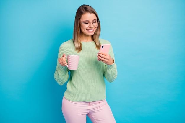 Portret van haar ze mooi uitziende aantrekkelijke mooie charmante schattig gericht vrolijk vrolijk meisje cacao drinken met behulp van digitaal apparaat geïsoleerd over heldere levendige glans levendige blauwe kleur achtergrond