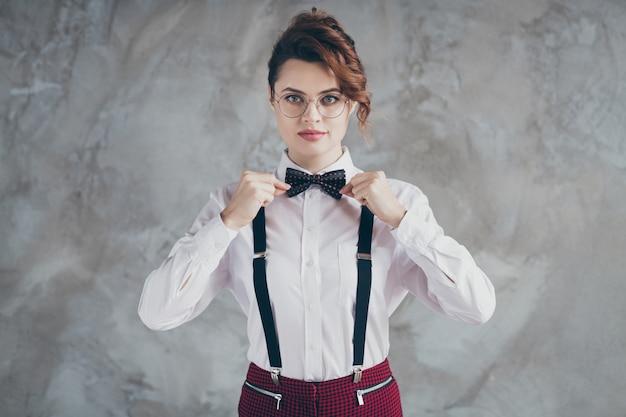 Portret van haar ze mooi uitziende aantrekkelijke mooie vrij serieuze stijlvolle elegante golvende haired meisje vaststelling van vlinderdas slijtage geïsoleerd over grijze betonnen industriële muur achtergrond