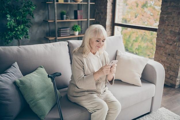 Portret van haar ze mooie aantrekkelijke mooie gericht vriendelijke grijsharige oma zittend op divan sms verzenden naar kleinkinderen pensioen uitgeven in industriële bakstenen loft moderne stijl interieur huis