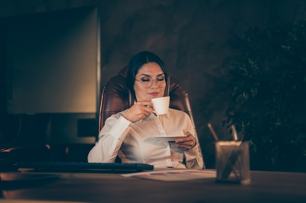 Portret van haar ze mooie aantrekkelijke mooie stijlvolle dame deskundige specialist econoom auditor advocaat advocaat bedrijfseigenaar zittend in stoel genieten van aromatische espresso 's nachts donkere werkplek station