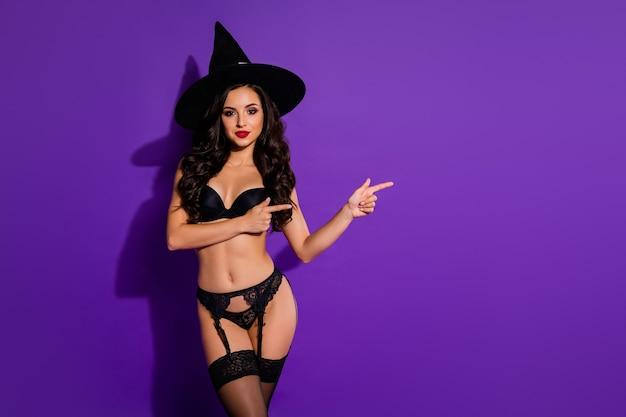 Portret van haar ze mooie aantrekkelijke prachtige zelfverzekerde zwarte brunette golvende dame wijst opzij aanbevelen advertentie advertentie geïsoleerd op heldere levendige glans levendige violet paars lila kleur achtergrond