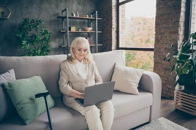 Portret van haar ze mooie aantrekkelijke rustige vriendelijke grijsharige dame zittend op een divan schrijven e-mail chatten zoeken website op industriële bakstenen loft moderne stijl interieur huis binnenshuis