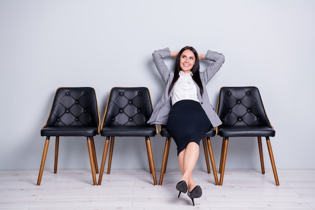 Portret van haar ze mooie aantrekkelijke stijlvolle elegante vrolijke dame executive office manager zittend in stoel rusten dromen vergadering ceo baas chief promotie geïsoleerde pastel grijze kleur achtergrond