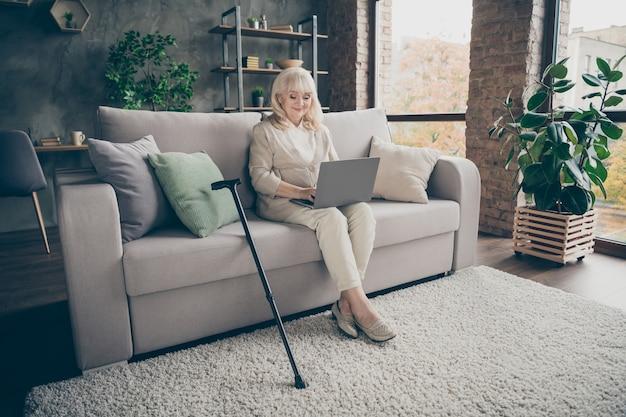 Portret van haar ze mooie aantrekkelijke vriendelijke vreedzame vriendelijke grijsharige dame zittend op een divan e-mail verzenden naar familieleden uitnodigend voor een bezoek aan industriële bakstenen loft moderne stijl interieur huis binnenshuis