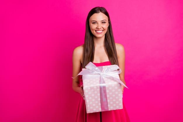 Portret van haar, ze ziet er leuk uit aantrekkelijk mooi innemend prachtig vrolijk langharig meisje in handen houden boog lint doos geïsoleerd op heldere, levendige glans levendige roze fuchsia kleur achtergrond
