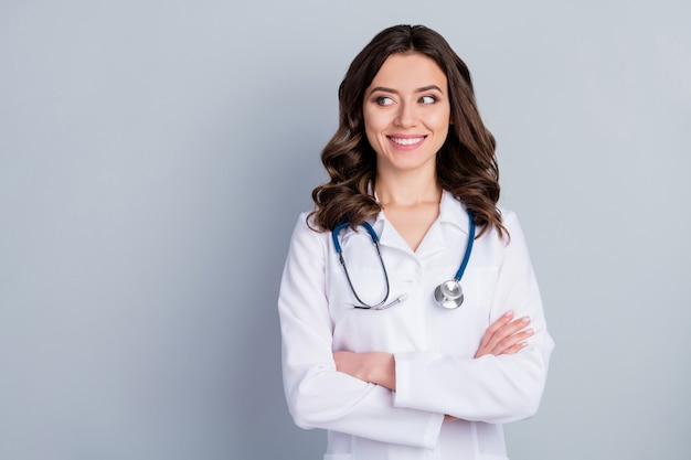 Portret van haar ze ziet er mooi uit aantrekkelijk mooie inhoud vrolijk vrolijk bekwaam golvendhaar meisje doc phonendoscope stethoscoop gevouwen armen geïsoleerd over grijze pastelkleur achtergrond