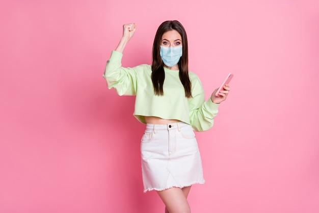 Portret van haar zij aantrekkelijk gezond gelukkig meisje draag gaasmasker met gadget vieren thuisbezorging verkoop winkel mers cov preventieve maatregelen geïsoleerde roze pastel kleur achtergrond