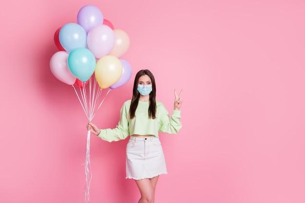 Portret van haar zij aantrekkelijk gezond mooi meisje draag veiligheidsgaasmasker met v-teken stop pandemia influenza mers cov thuis blijven besmetting preventie geïsoleerde roze pastel kleur achtergrond