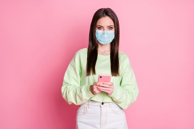 Portret van haar zij aantrekkelijk mooi mooi meisje dat een veiligheidsgaasmasker draagt met behulp van apparaat thuisbezorging bestellen app winkel mers cov ziekte pandemie preventie geïsoleerde roze pastel kleur achtergrond