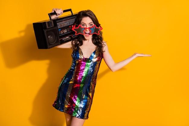 Portret van haar zij-uitziende aantrekkelijke vrolijke vrolijke golvende haired meisje met boombox houden op palm kopie ruimte advertentie nieuwigheid geïsoleerd heldere levendige glans levendige gele kleur achtergrond