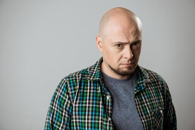 Portret van haatdragend triest emotionele man over beige muur