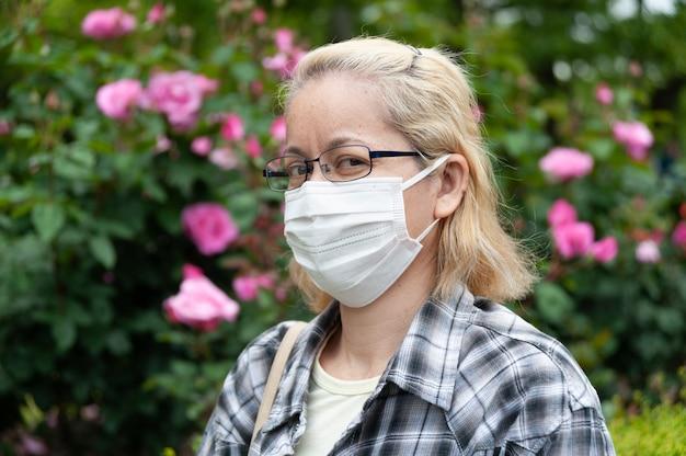 Portret van halfbloed blonde vrouw van middelbare leeftijd met oogglazen die wit chirurgisch masker dragen