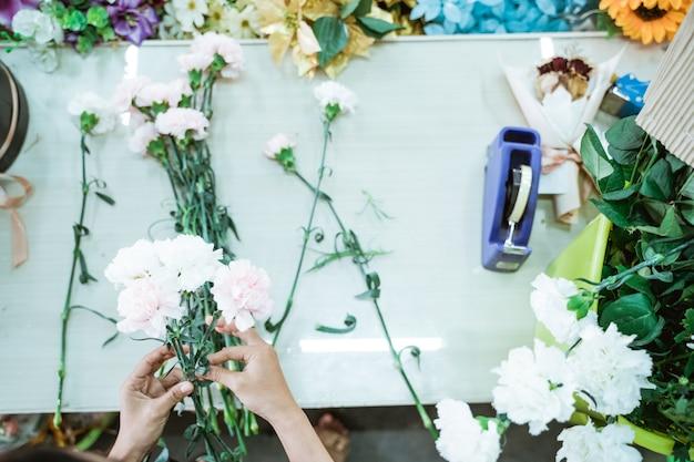 Portret van handbloemist maakt een bloemhandwerk op tafel
