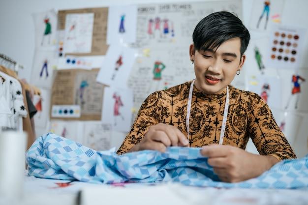 Portret van happy professionele aziatische jonge mannelijke kleermaker met meetlint op nek werken