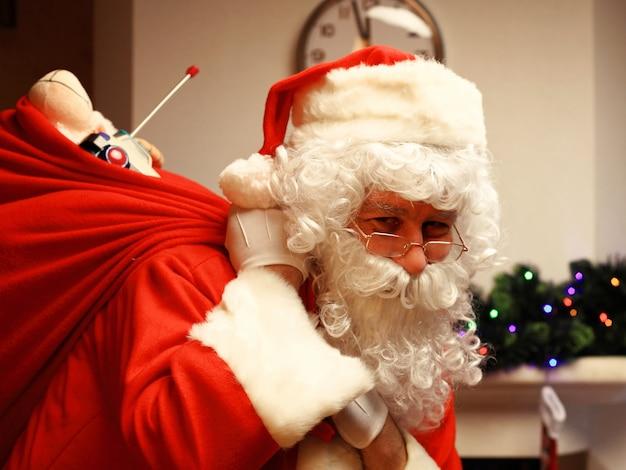 Portret van happy santa claus zak met geschenken te houden en camera te kijken